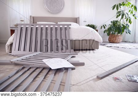 Instructions And Components For Self Assembly Baby Cot On Bedroom Floor