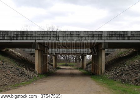 A Concrete Road Bridge Crossing Over A Country Dirt Trail