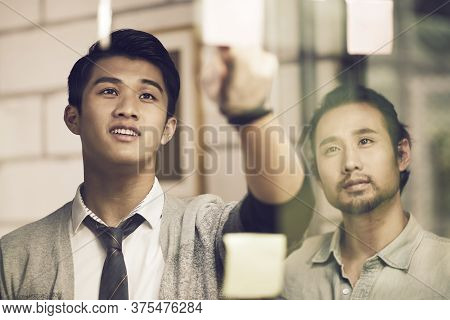 Two Asian Small Company Businesspeople Young Entrepreneurs Meeing Discussing In Office Using Sticky