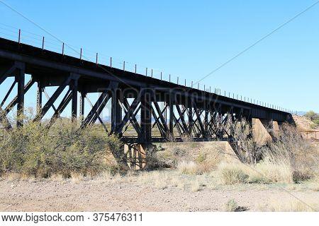 A Tall Railway Bridge Over A Desert Gorge With Blue Sky