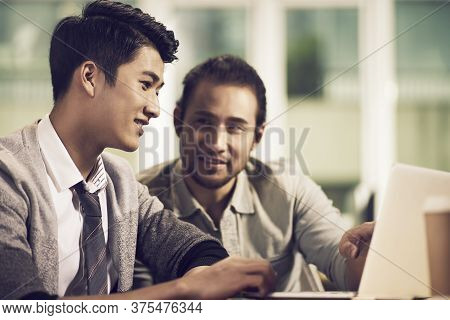 Two Young Asian Entrepreneurs Discussing Business Using Laptop Computer In Office