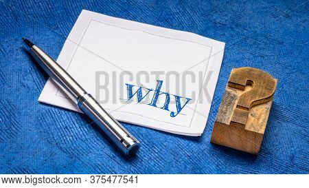 why question on a napkin with vintage letterpress wood type question mark against against blue bark paper, curiosity, explanation and reason concept