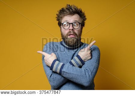 Shaggy Man With A Strange, Dumb Grimace Got Confused, He Crossed Arms And Shows Fingers In Different