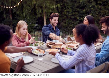 Multi-Cultural Friends At Home Sitting At Table Enjoying Food At Summer Garden Party