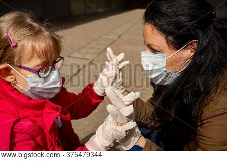 Mother Embrace Her Frighten Daughter, They Have A Medical Gloves And Masks For Protection Against Vi