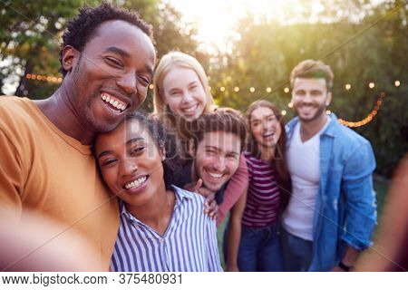 Group Of Multi-Cultural Friends Posing For Selfie As They Enjoy Outdoor Summer Garden Party