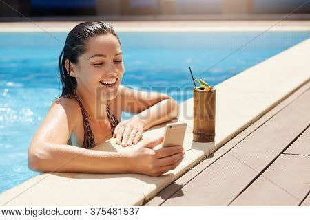 Happy Smiling Female With Wet Hair Holding Modern Smart Phone In Hand, Relaxing At Poolside And Drin