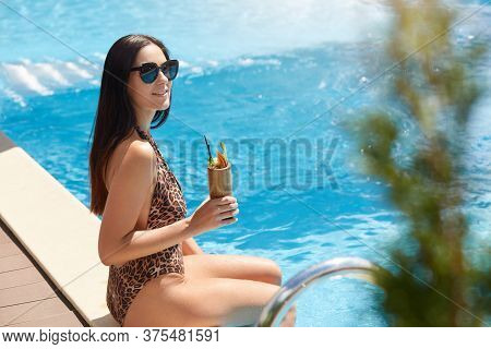 Happy Young Woman With Cocktail Sitting At Poolside, Lady Resting In Luxury Recreation Center, Lady