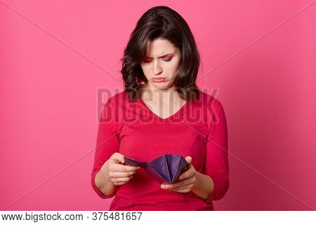 Depressed Young Woman Looking Into Her Purse With Sad Facial Expression, Having No Money, Dark Haire