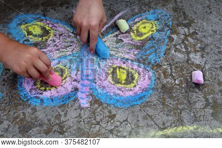 Children\'s Drawings On The Pavement. Children Draw Butterflies With Chalk On The Pavement.