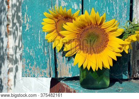 A Bouquet Of Sunflowers In A Glass Jar On The Windowsill. Rural Still Life. Copy Space