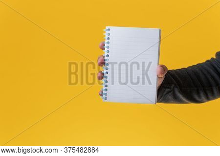 Male Hand Showing A Blank Note Pad Towards The Camera Over Yellow Background.