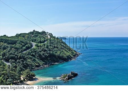 Top View Of A Large Green Island With A Dense Forest. Sunny Summer Day, Blue Sky. In A Calm Aquamari