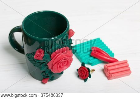 Cup Decorated With Polymer Clay Roses, Handmade. Nearby Are Pieces Of Polymer Clay Of Different Colo