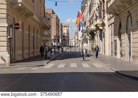 Rome, Italy - 12 March 2020: A Man With A Face Mask Walks Down Via Del Corso Amongst Few Passersby,