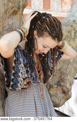 Indie style woman with dreads, ornamental dress