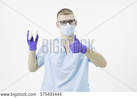 Young Handsome Intern Doctor Dentist Wearing Glasses And Protective Mask Holds A Model Of Molar Toot