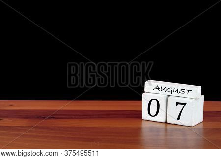 7 August Calendar Month. 7 Days Of The Month. Reflected Calendar On Wooden Floor With Black Backgrou