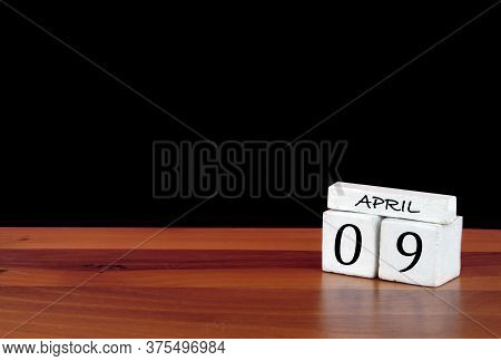 9 April Calendar Month. 9 Days Of The Month. Reflected Calendar On Wooden Floor With Black Backgroun