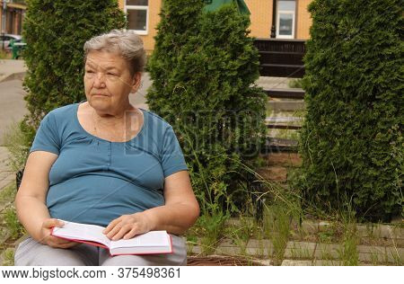 An elderly woman is sitting in the courtyard on a summer day, reading a book and sometimes thinking