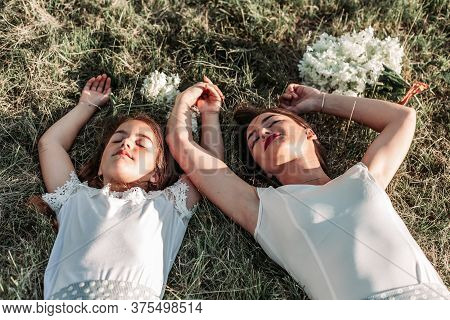 Mom And Her Daughter Lying On The Grass With Arms Above Theirs Heads