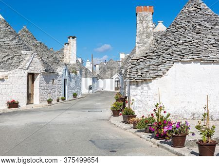 Winding street with typical Trulli houses in Alberobello, Apulia, Italy.