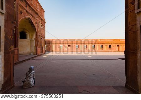 Agra, India - 4 May 2015: A Woman With Her Head Covered Is Sitting In The Shade, Looking At A Desert