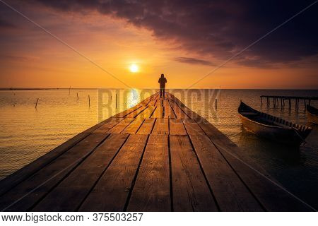 Lonely Person Standing On A Pontoon Meditating And Enjoying The Sunrise Or Sunset On A Lake With A F