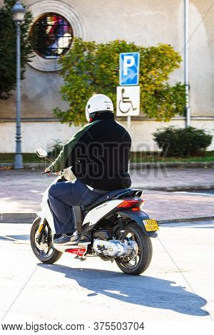 Back View Of Man Riding A Moto Scooter In Downtown Of Lugoj, Romania, 2020.