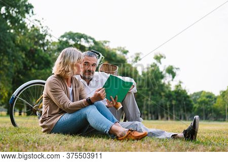 Caucasian Elderly Couple Relaxing And Sitting At The Park Reading The Retirement Plan To Discussing