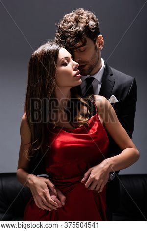 Handsome Man In Suit Embracing Sensual Woman In Red Dress On Grey