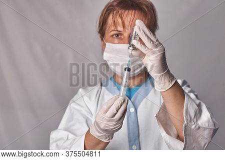 The Doctor Gets The Vaccine Into The Syringe. Glass Bottle In A Technicians Hand. A Bottle With A Cu