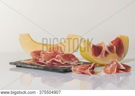 Thin Slices Of Cured Ham On A Dark Plate Surrounded By Melon Slices, One Of Them With Cured Ham On T