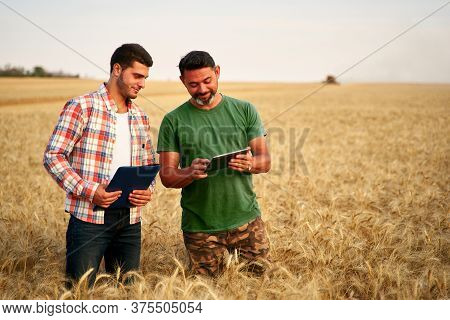 Two Farmers Stand In Wheat Stubble Field, Discuss Harvest, Crops. Senior Agronomist With Touch Table