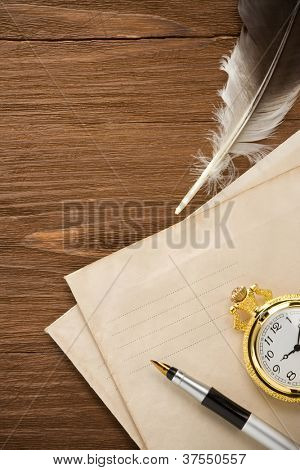 watch and ink pen at envelope on vintage wood background texture
