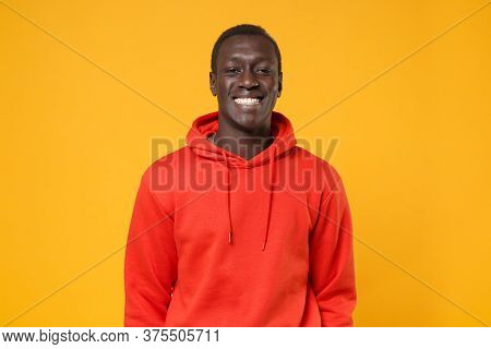 Smiling Young African American Man Guy In Red Streetwear Hoodie Posing Isolated On Yellow Background