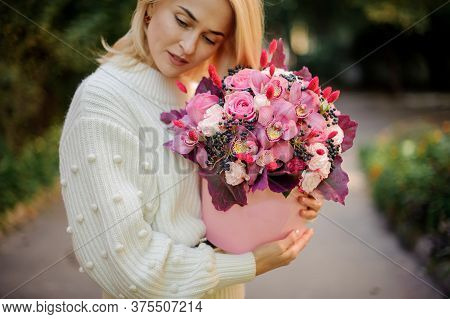 Beautiful Woman Neatly Holds Pink Round Box With Flowers Inside