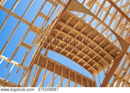 New Construction Home Framing Against Blue Sky. Ceiling Frame And Arch Structure Details.