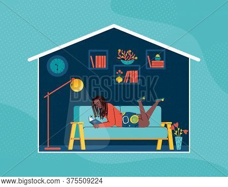 A Young Girl Is Lying On The Sofa And Reading A Book Near The Floor Lamp. A Woman Spends Her Evening