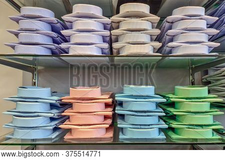 Folded Mens Shirts In A Store. Shelves With A Lot Of Colorful Shirts Neatly Folded In The Store Clot
