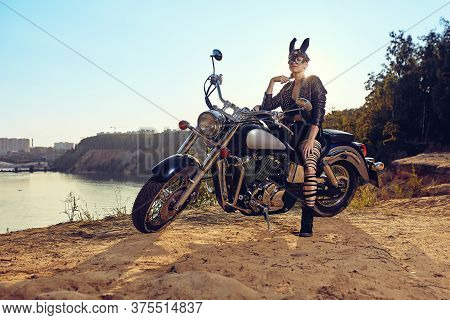 A Beautiful Sexy Young Woman In Leather Jackets And Rabbit Mask Sitting On A Black And Chrome Motorb