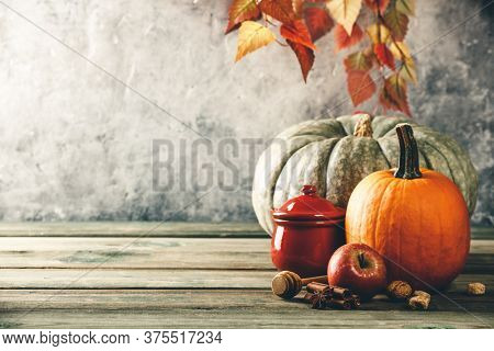 Autumn background with cup of tea or coffee, pumpkins, pumpkin pie spices and leaves on wooden tabel against old rust condition vintage wall, space for text