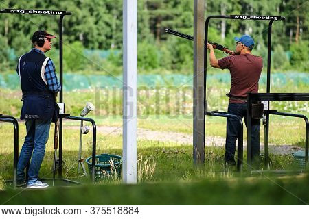 Two Shooters In The Shooting Range Of The Bench. The Man Is Wearing Headphones, The Second Is Ready
