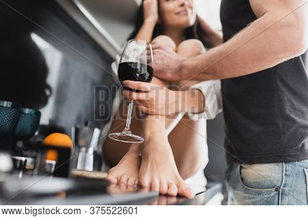 Selective Focus Of Man Embracing Sexy Girlfriend In Shirt With Glass Of Wine On Kitchen Worktop
