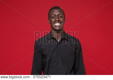 Smiling Young African American Man Guy In Classic Black Shirt Posing Isolated On Red Wall Background