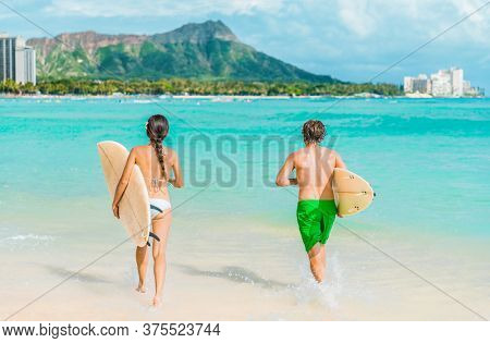 Hawaii Honolulu couple surfers going surfing on waikiki beach with surfboards running in water. Healthy active sport lifestyle fitness people at diamond head mountain landscape.