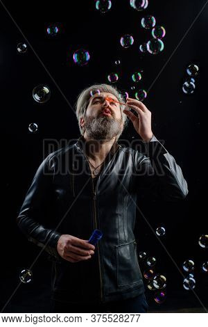Soap Bubbles. Man Play With Bubbles. Man Blowing Bubbles. Bearded Man Blowing Soap Bubbles. Happines