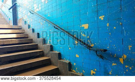 Old Exit From The Underpass Of A Staircase With A Railing Against The Background Of A Blue Shabby Wa