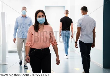 People In Office Following Social Distancing Protocols Wearing Face Masks