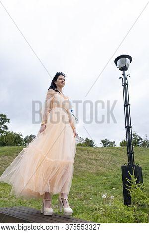 Young Girl In A Long Evening Dress On An Impromptu Catwalk